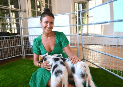 sasha filimonov holding two mini piglets on her lap in london