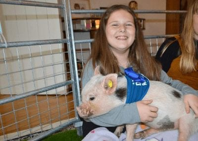 a girl cuddling a micro pig at a party in london